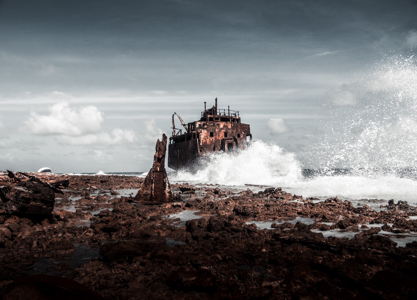 Waves crashing on rock with a derelict building in the background