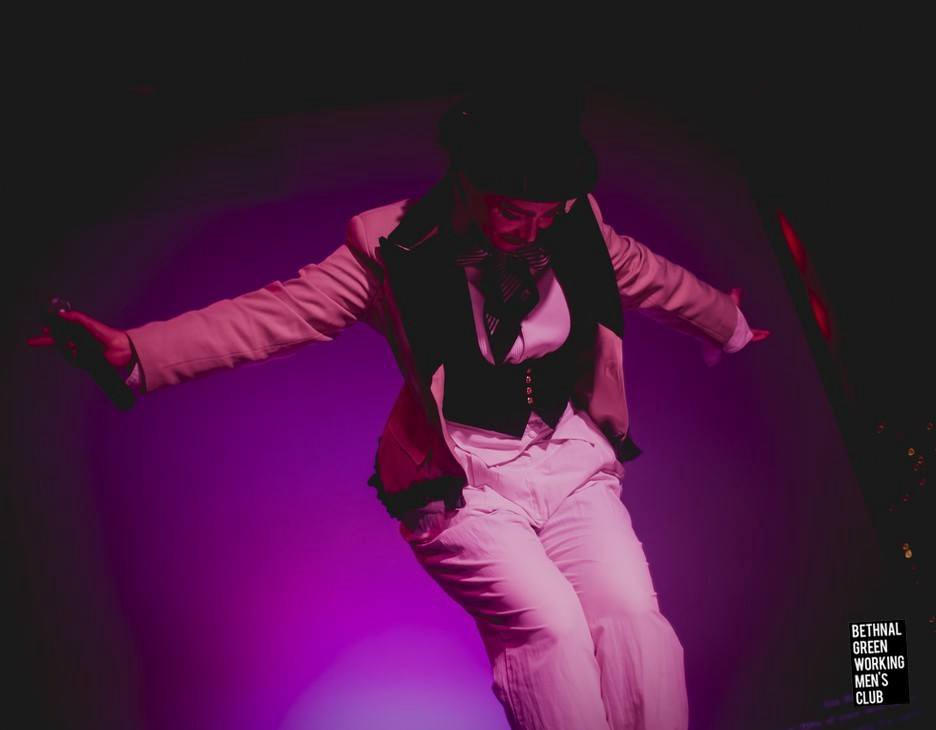 A woman bows onstage in a purple spotlight. She is wearing a cream coloured jacket with black trim, a white shirt and white dandy trousers, a black waistcoat, a black and white striped neckerchief and black top hat. On the left hand-side of the image is the text, ´Bethnal Green Working Men´s Club´.
