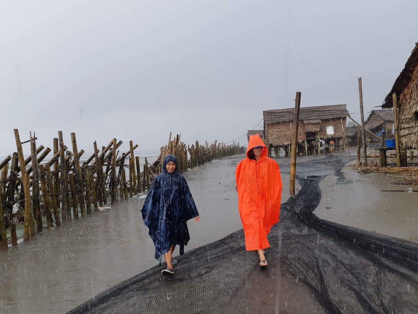 Two intrepid researchers walking through a small fishing village, with thatch huts and wooden fencing, in a torrential downpour.