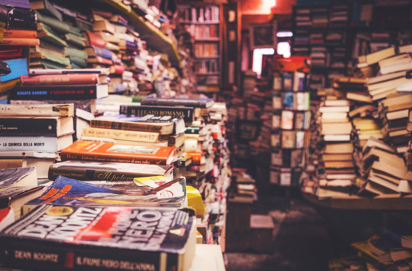 Piles and piles of books in a crowded store.