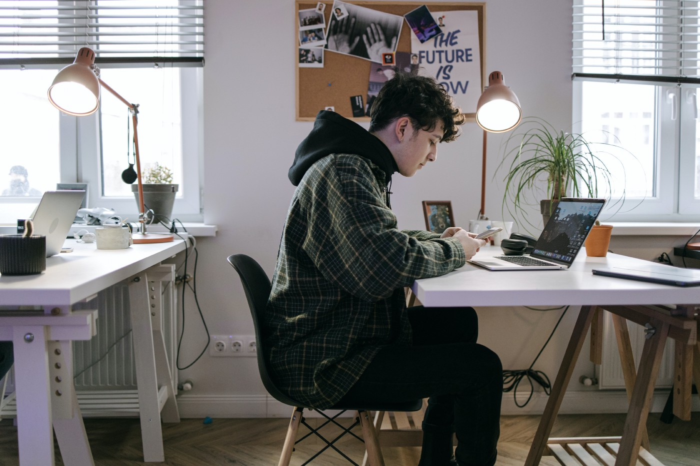 Young man at desk reading from mobile phone