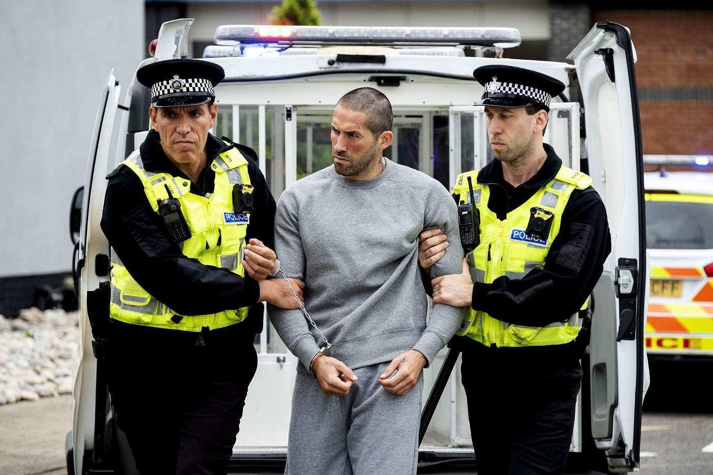 Production still from Avengement (2019) with Scott Adkins (as Cain Burgess) in the middle of two police officers, being escorted by them.