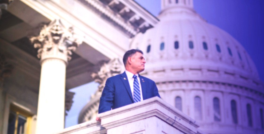 US Congressman Andrew Clyde in a blue suit, on the corner of a balcony, posing in profile with the US Capitol dome in the background