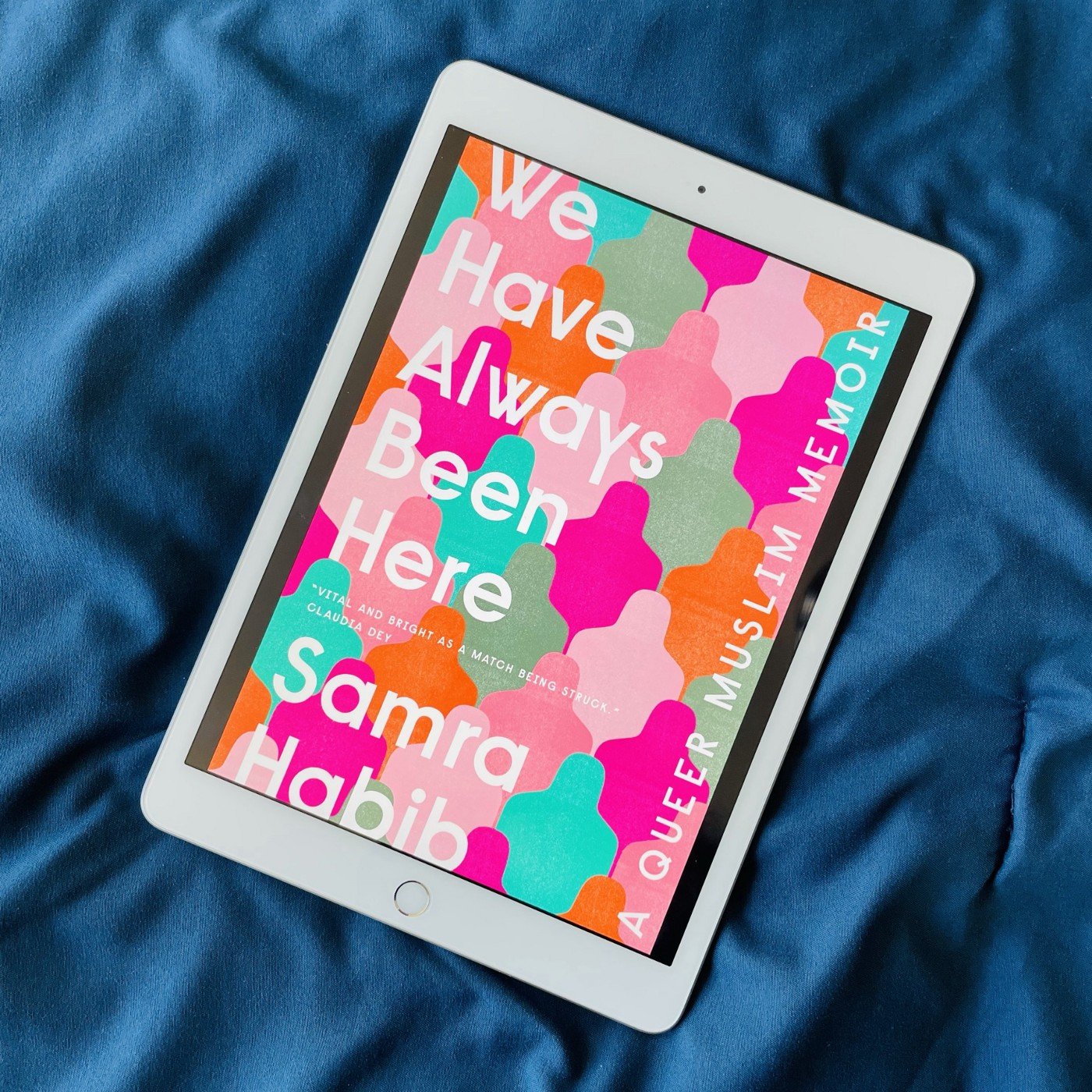 Kindle e-reader on a satin, navy fabric, showing the cover of 'We have always been here', a queer memoir.