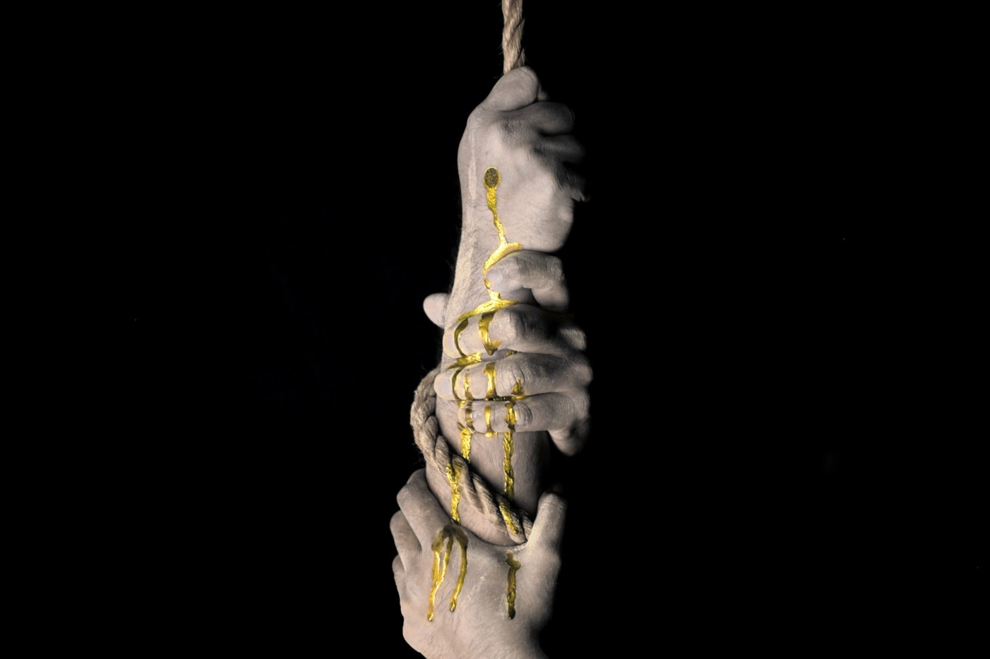Three hands vertically grip a rope, one on top of the other against a black background. The top hand has a wound which bleeds