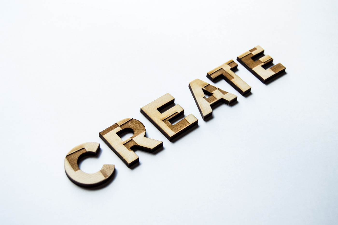 The word 'create' is spelt out in capitalised wooden letters against an off-white backdrop.