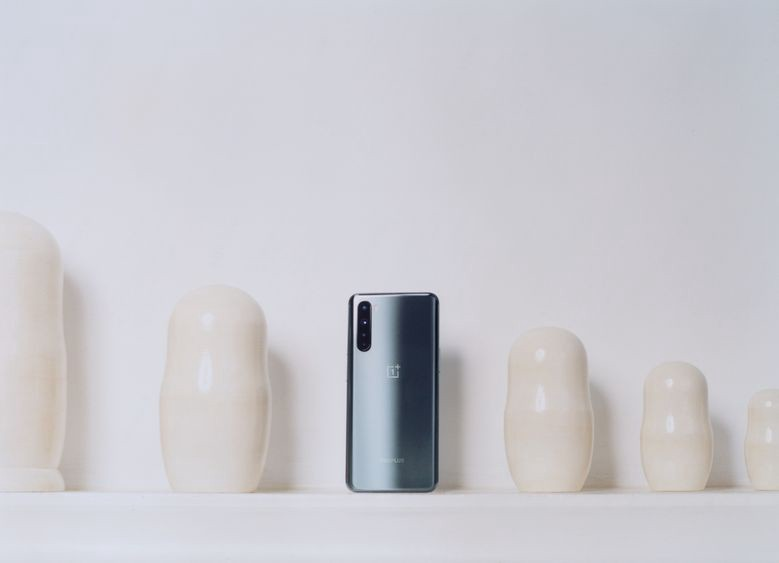 A promotional photo of a OnePlus Nord phone against a wall with cream-colored ceramics.