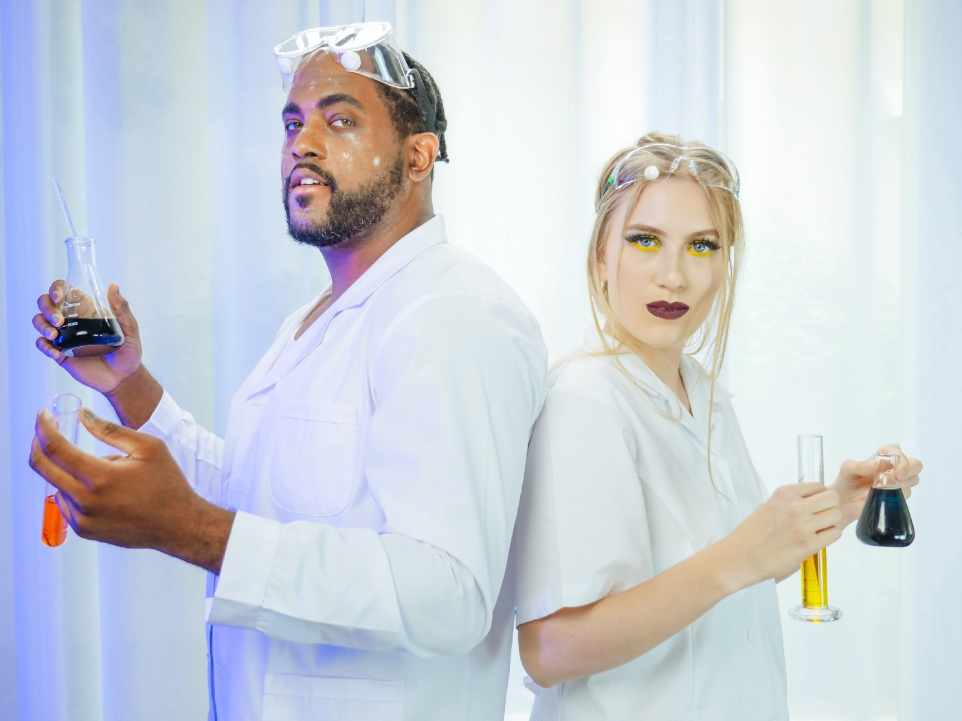 A man and a women dressed in scientists' coat hold chemicals in their hands