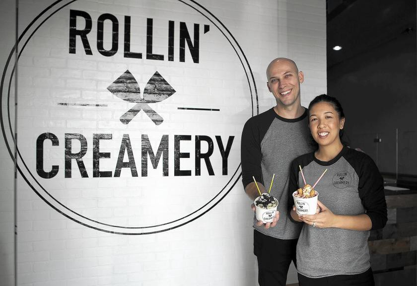"""A man and woman stand in front of a white brick wall smiling and holding up cups of rolled ice cream. The wall says """"Rollin' Creamery"""" in black and features a drawing of two spatulas in the middle"""