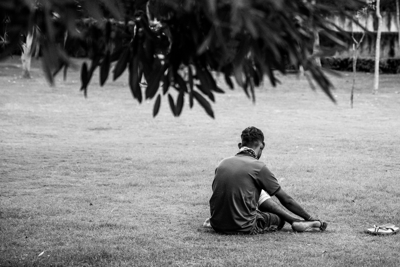 Man sitting alone, posture indicates he's tired or sad.