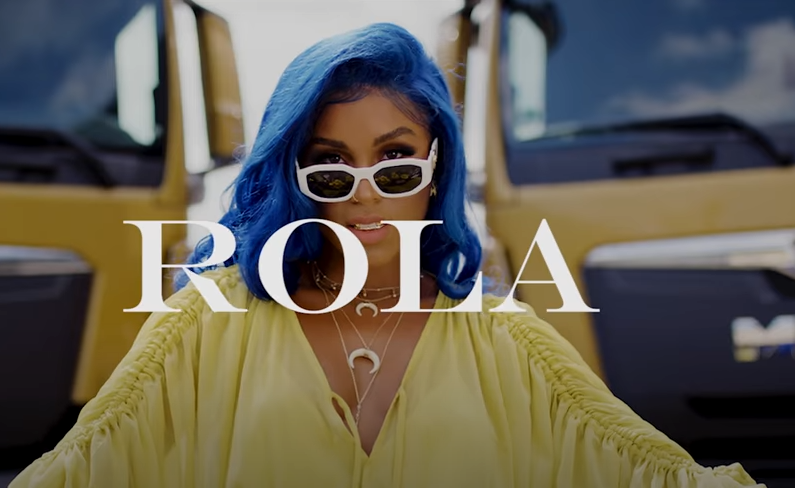 Hi there! BichoDoMato here. This is a picture of the German singer Rola. On this picture, she had blue hair (!), wearing a yellow blouse, nice half-moon necklace. She is looking over her white eyeglasses. She is totally…gorgeous.
