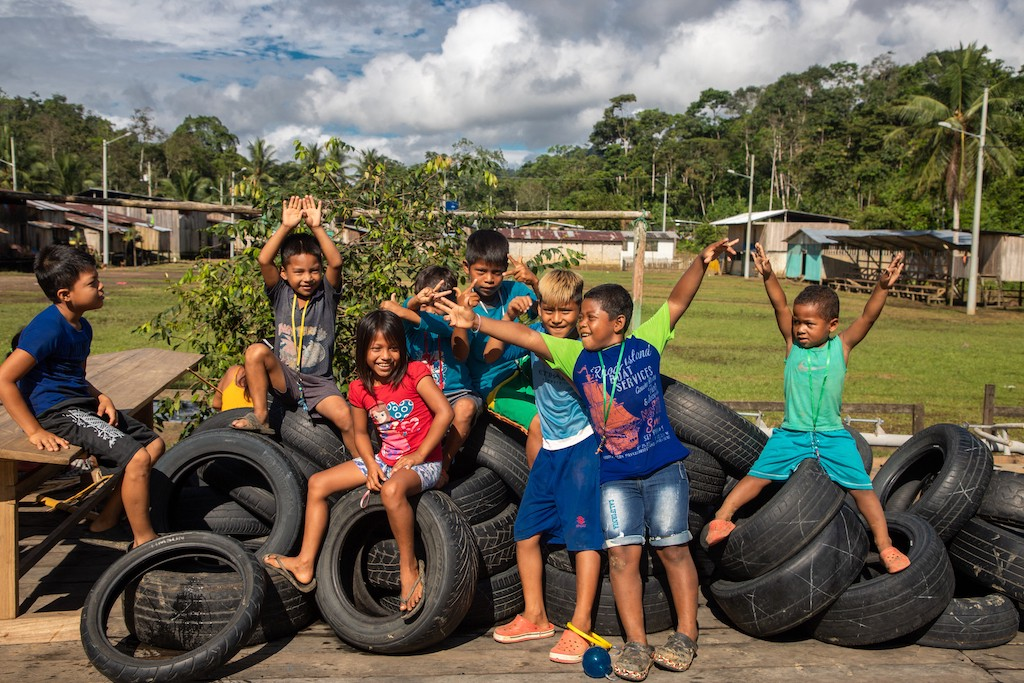 Children of the Chachi tribe pose and play on a pile of discarded tires.