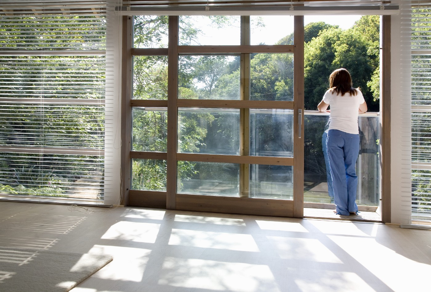 View through an empty room of a woman standing on a balcony.