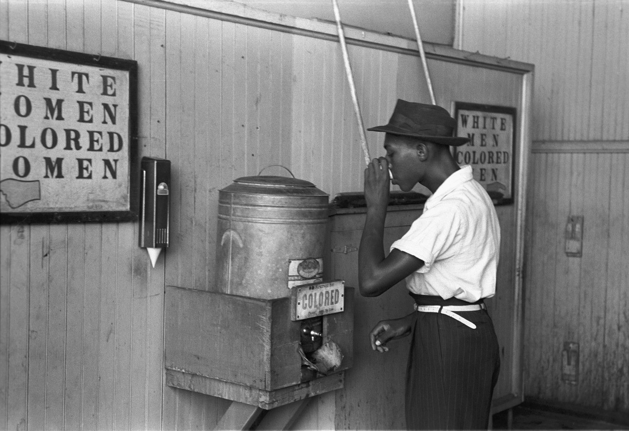 "A man drinks at a water cooler marked ""colored"" in a streetcar terminal in Oklahoma City, Oklahoma. Photograph circa 1938."