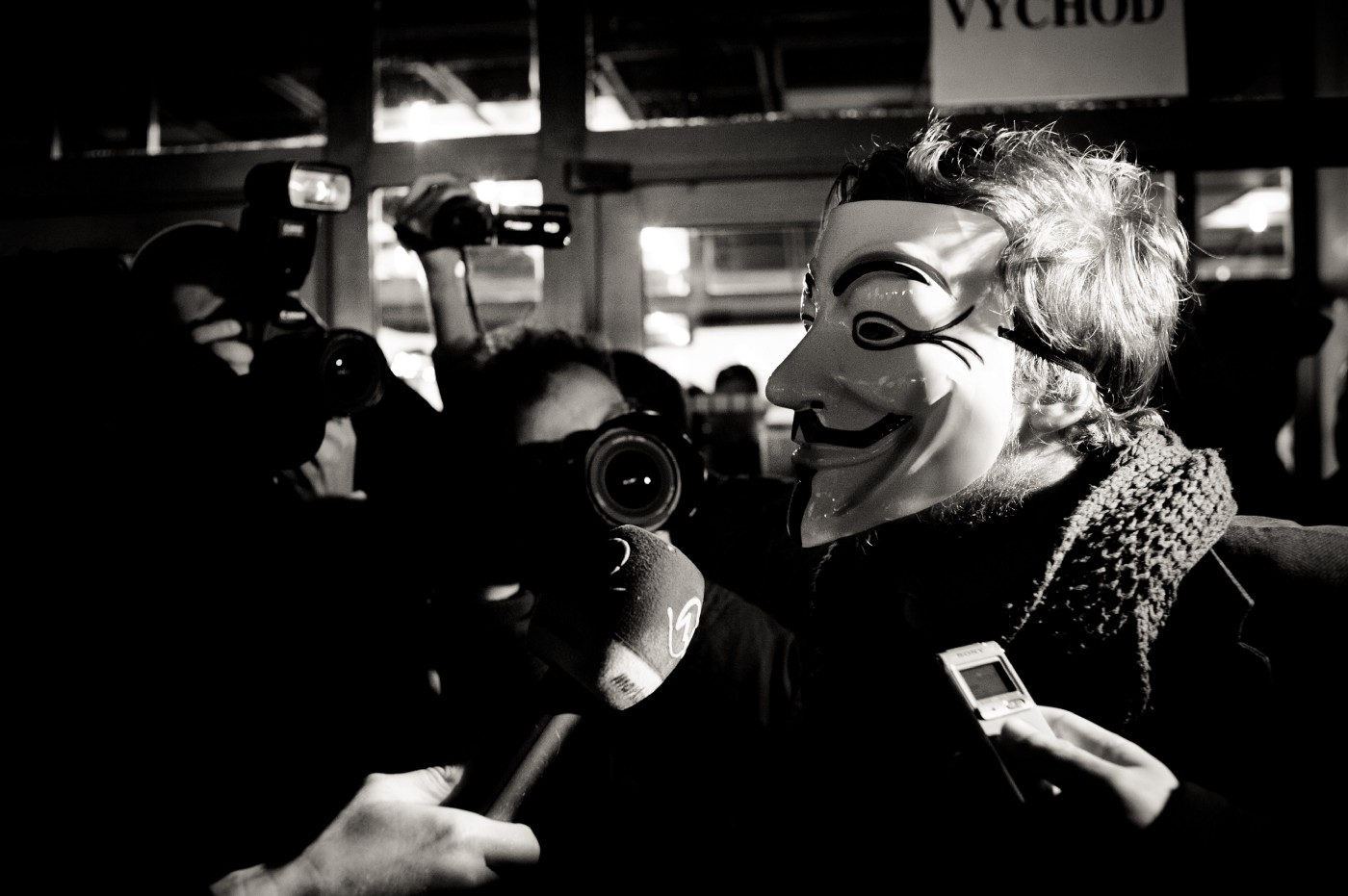 A masked man surrounded by paparazzi