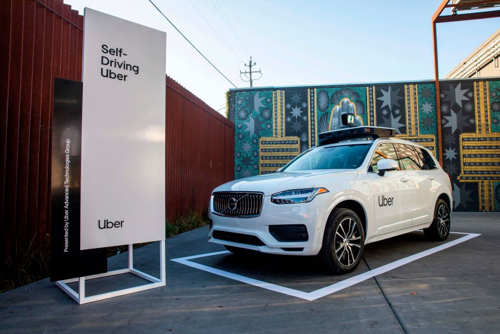 """A photo of an Uber self driving car on display with a sign that reads """"Self-Driving Car"""" to the left."""