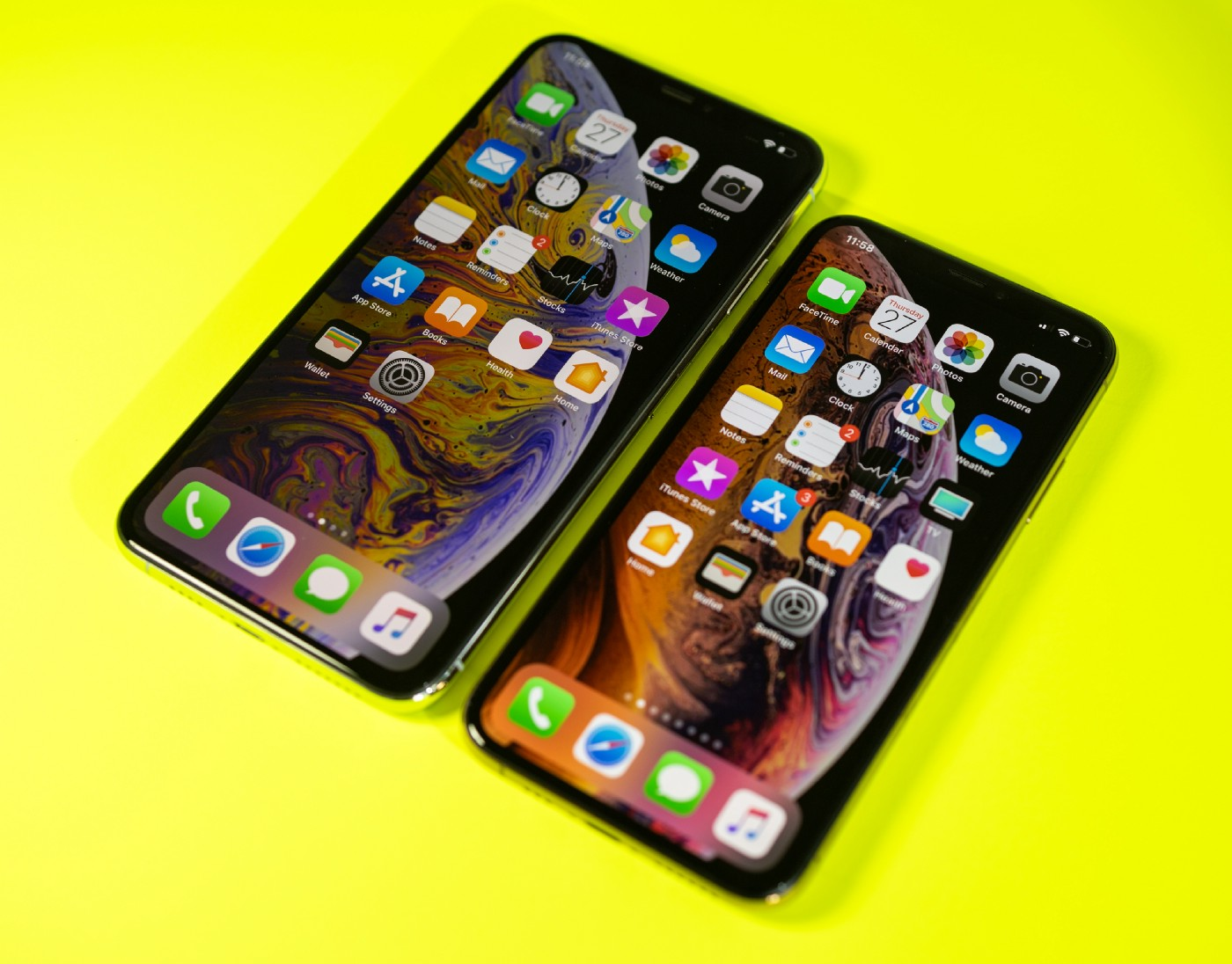 The new Apple iPhone Xs and Xs Max against a bright modern neon yellow background.