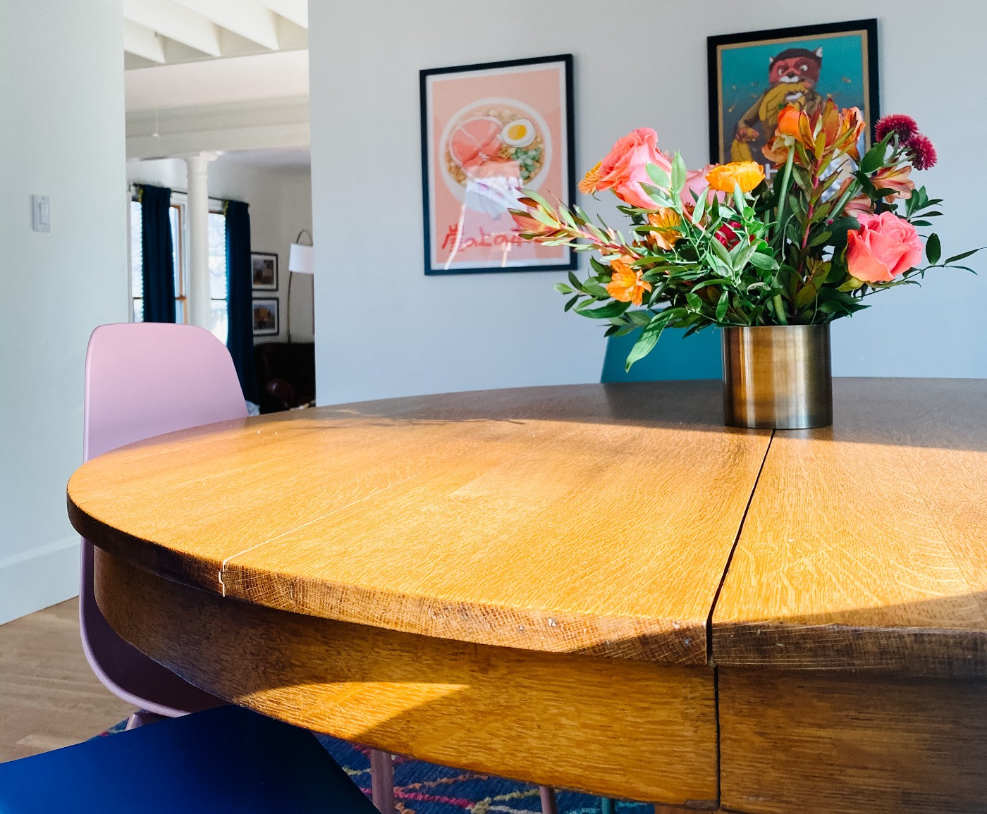 A rounded wooden table with a vase of flowers on it in a living room.