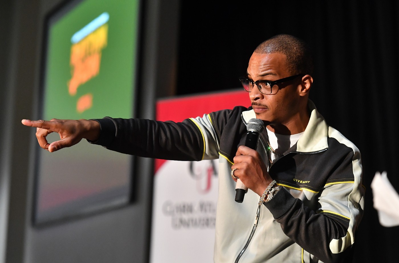 A photo of T.I. onstage pointing with his left arm into the crowd.