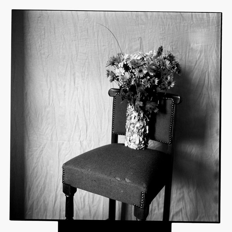 Black & White photograph of a bouquet of flowers standing on a chair.