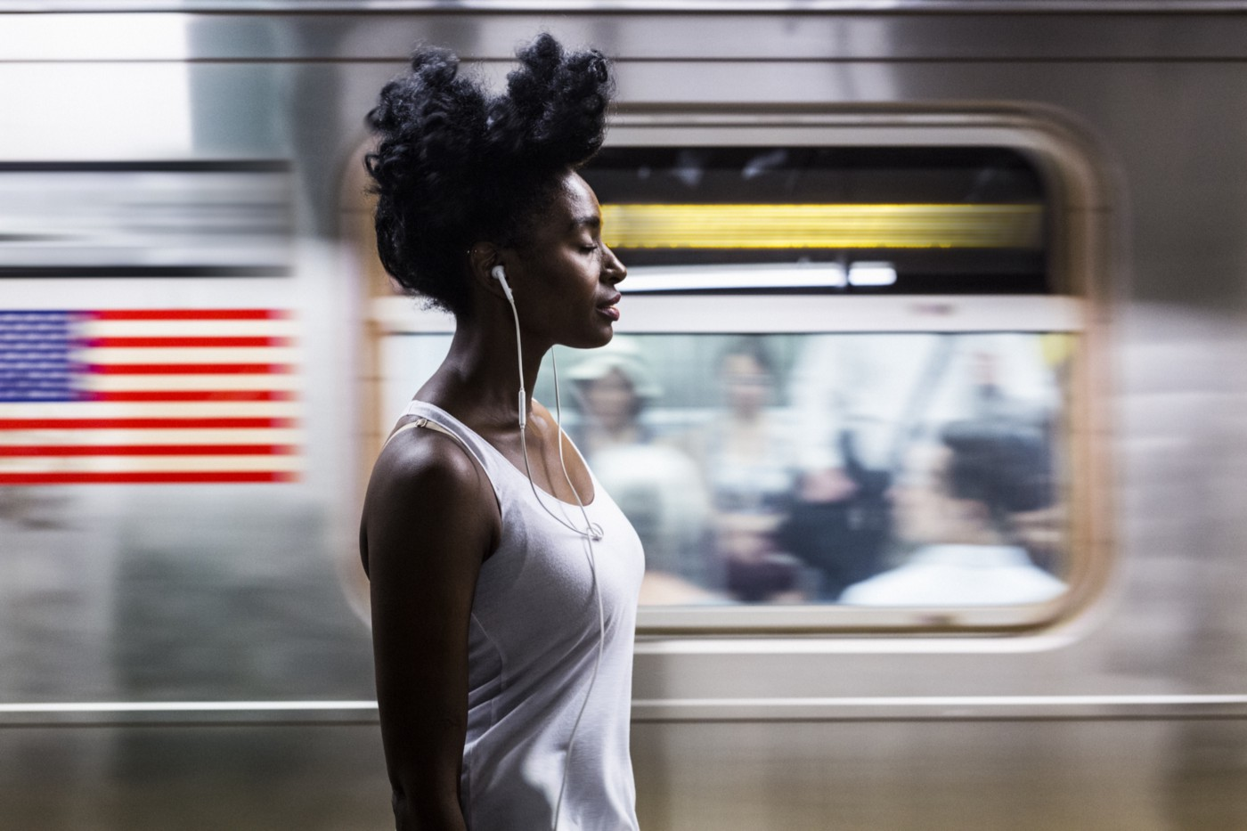 Black woman with eyes closed as subway passes by.
