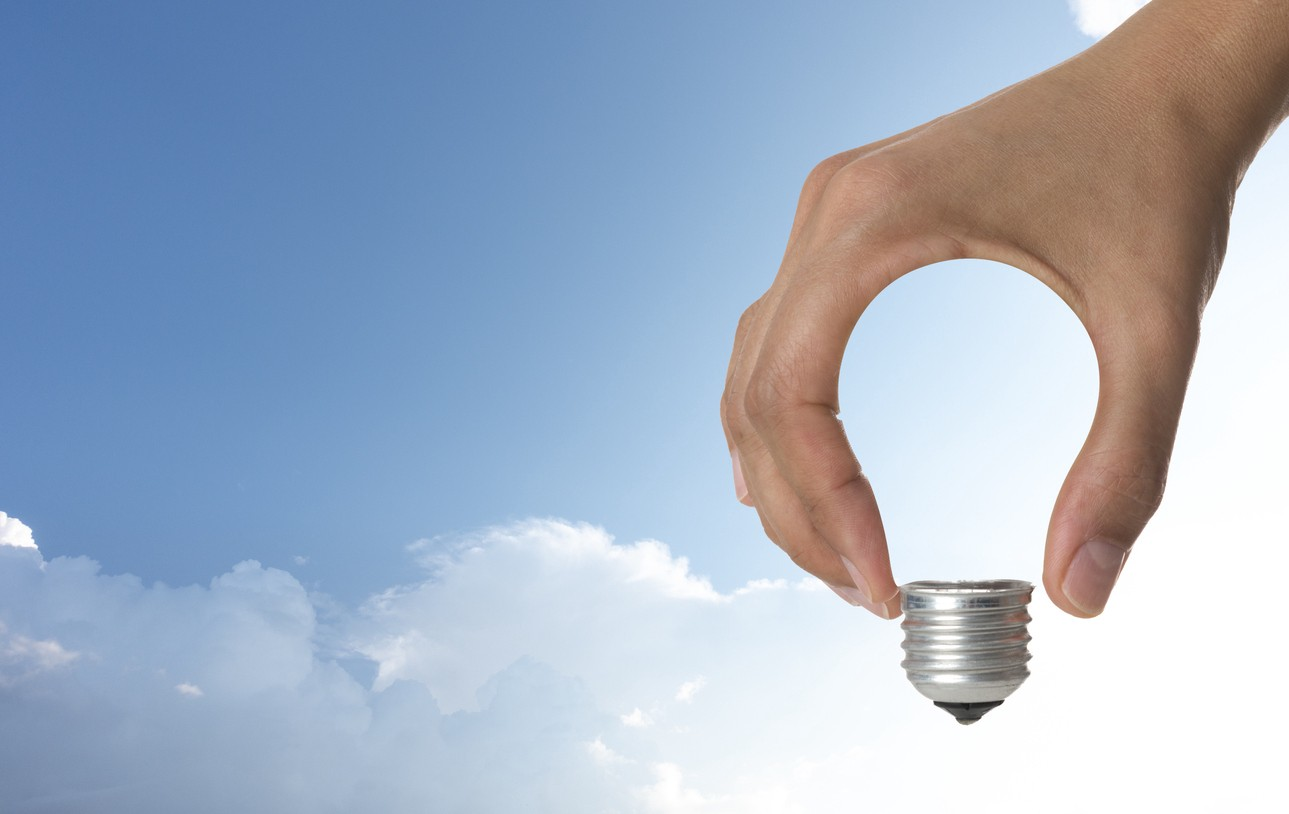 Image of a hand in the shape of a light bulb with clouds in background.