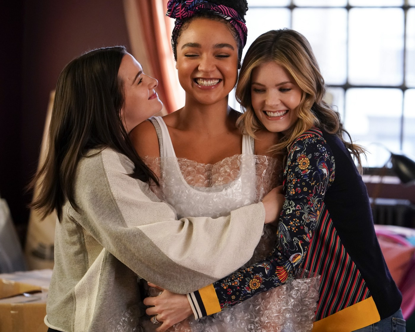 Three women, who are friends, hugging each other in a moment of tenderness.