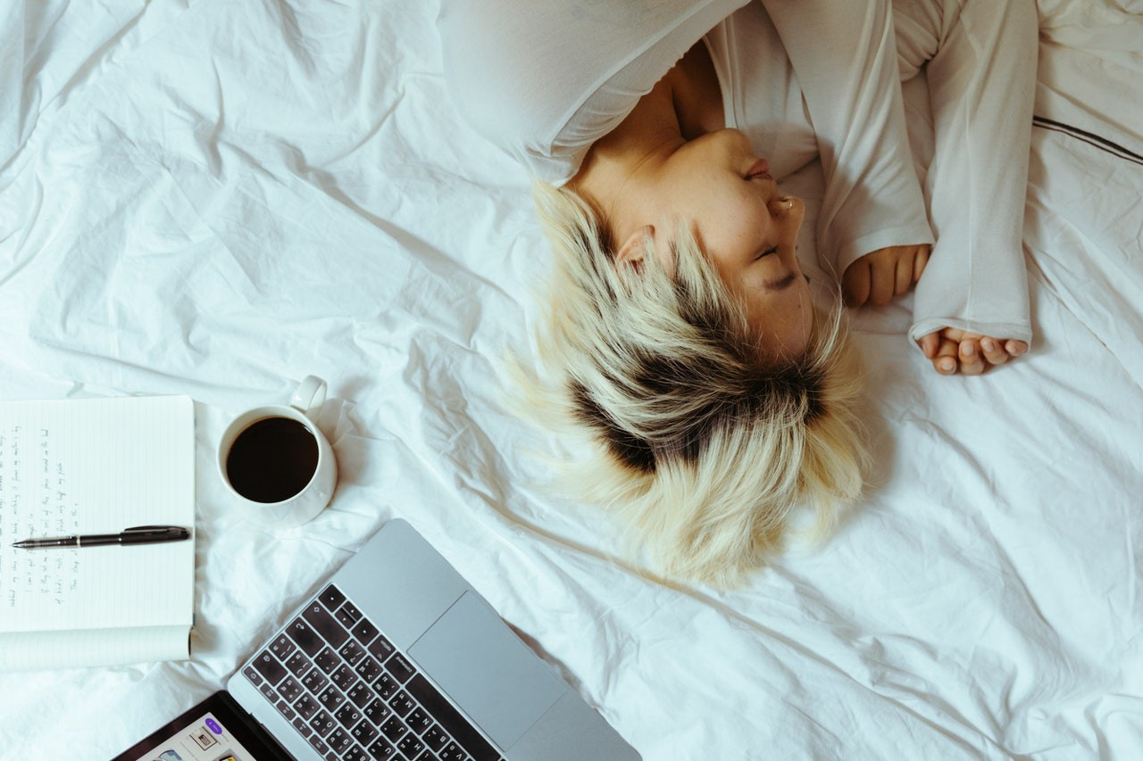 woman sleeping on a bed with laptop and open notebook nearby