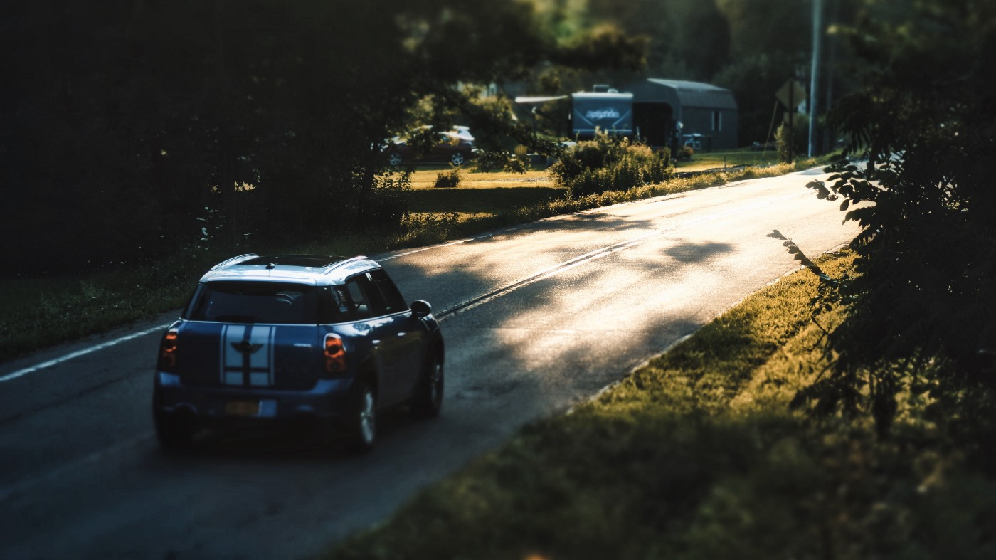 A blue and white Mini Cooper drives on a country road in dappled light.