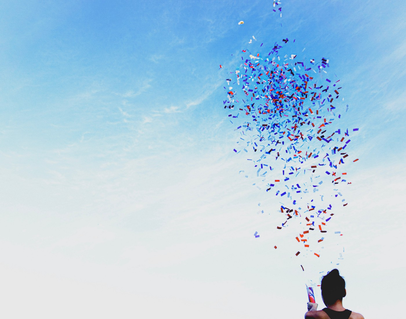 person shooting colorful confetti up against a blue sky