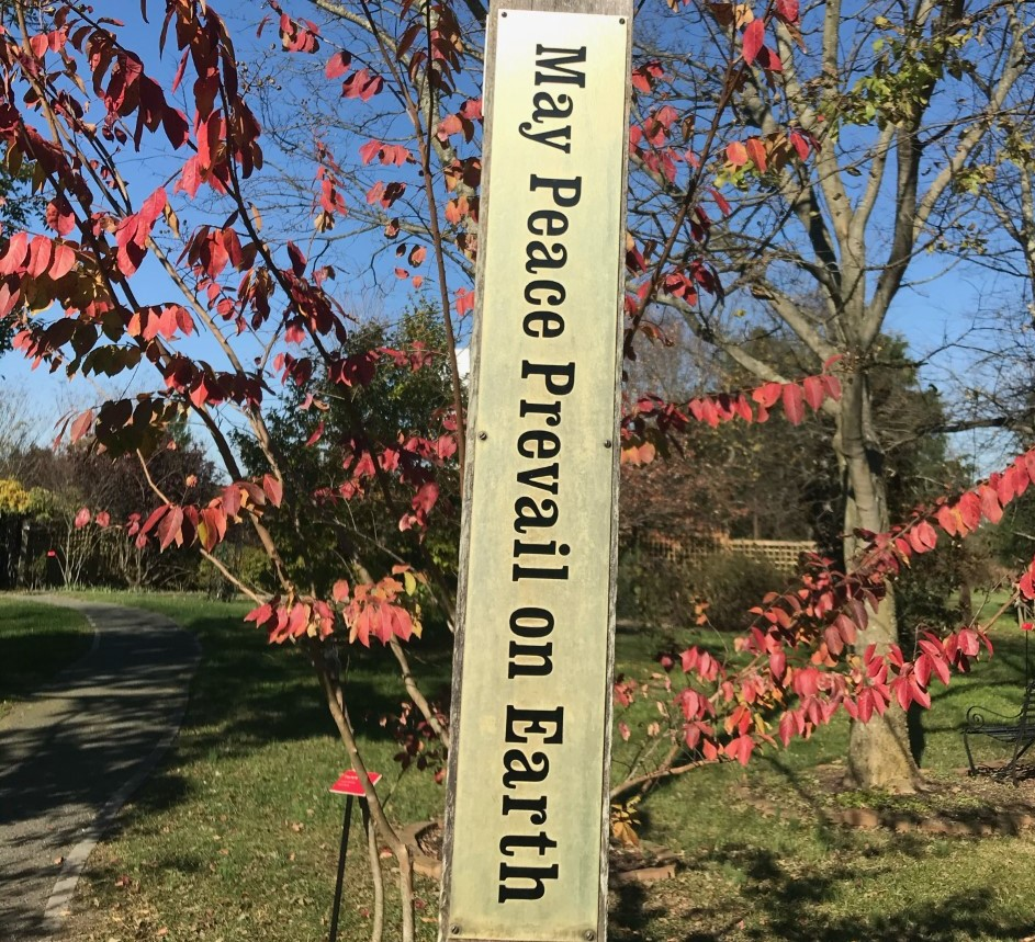 "Post says ""May Peace Prevail on Earth"" in front of tree with rose-colored leaves at St. Benedict Monastery, Bristow, VA."