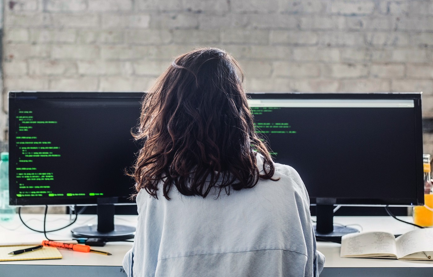 A female product designer reviews code. She is facing two computer monitors and has her back facing the camera.