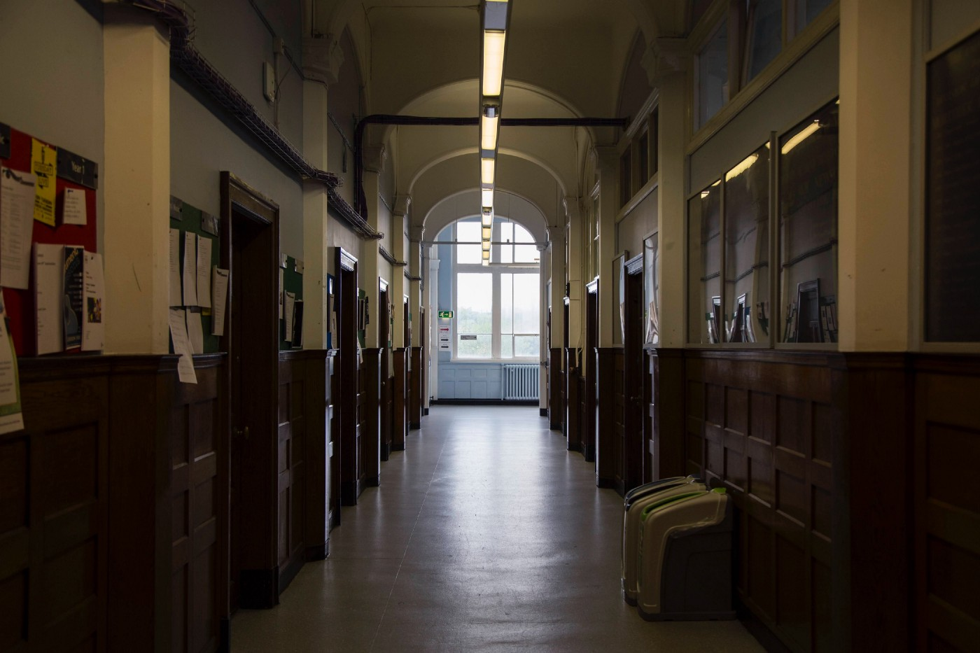 Photo of a dimly lit school hallway with a large window at the end of it.