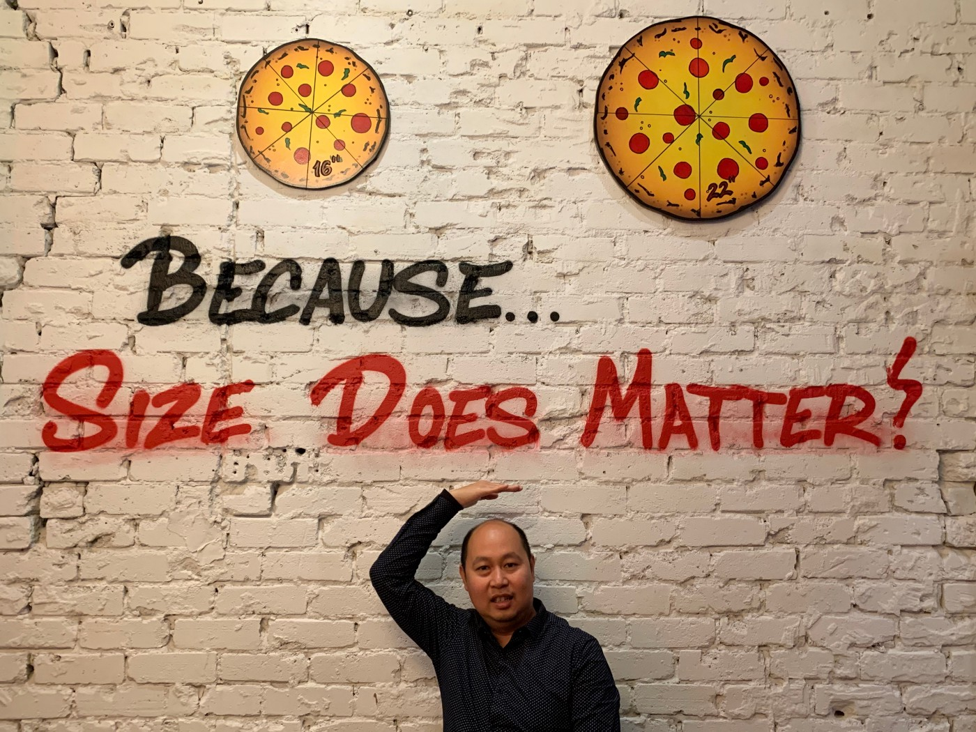 """The author in front of the sentence—written on a wall—""""Because… Size Does Matter!"""""""