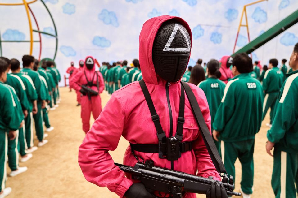 A guard from the Netflix series Squid Game holding a gun having a triangle on his mask wearing a magenta jumpsuit