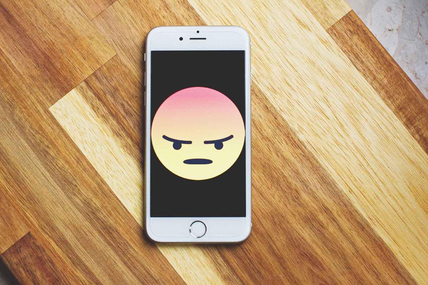 An white Apple iPhone with an image of an angry face emoji.