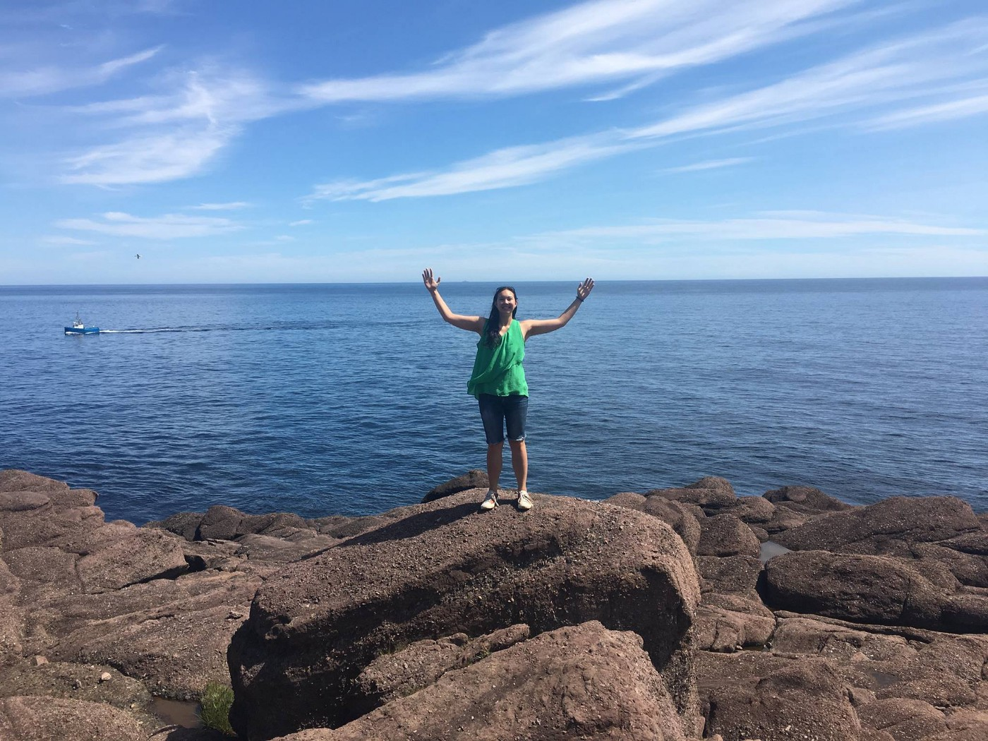 The author stands on a rock with her arms in the air. The ocean is in the background.
