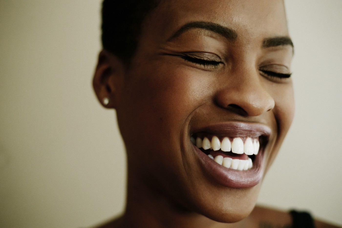 A closeup of a black woman smiling/laughing widely.