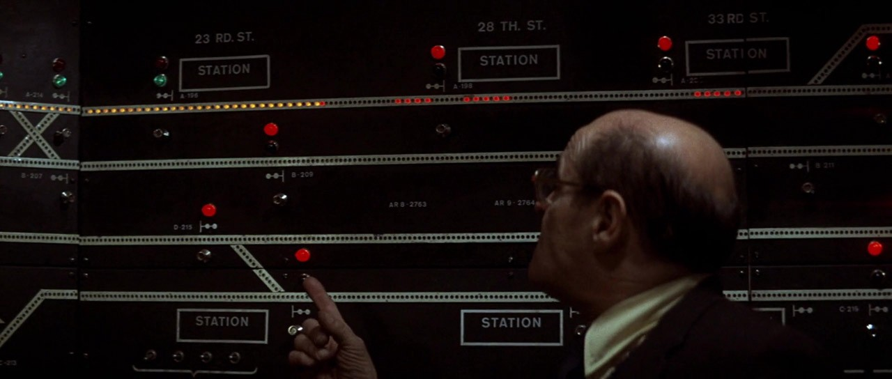 A man points to lightbulb-based subway route ladders in a control room