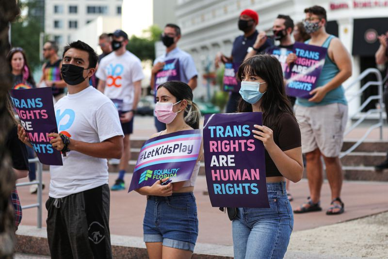 """Masked protestors of different genders and races stand with signs that read """"Trans Rights are Human Rights"""" and """"#LetKidsPlay Equality Florida"""""""