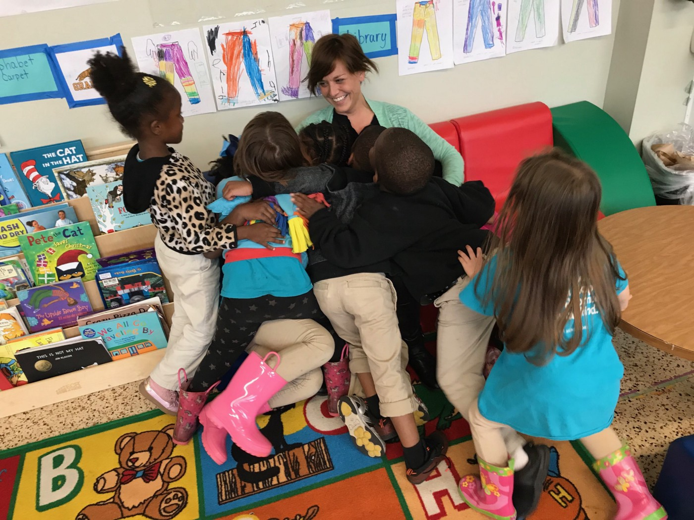 A smiling teacher sitting on a small couch under a pile of students who are hugging them.