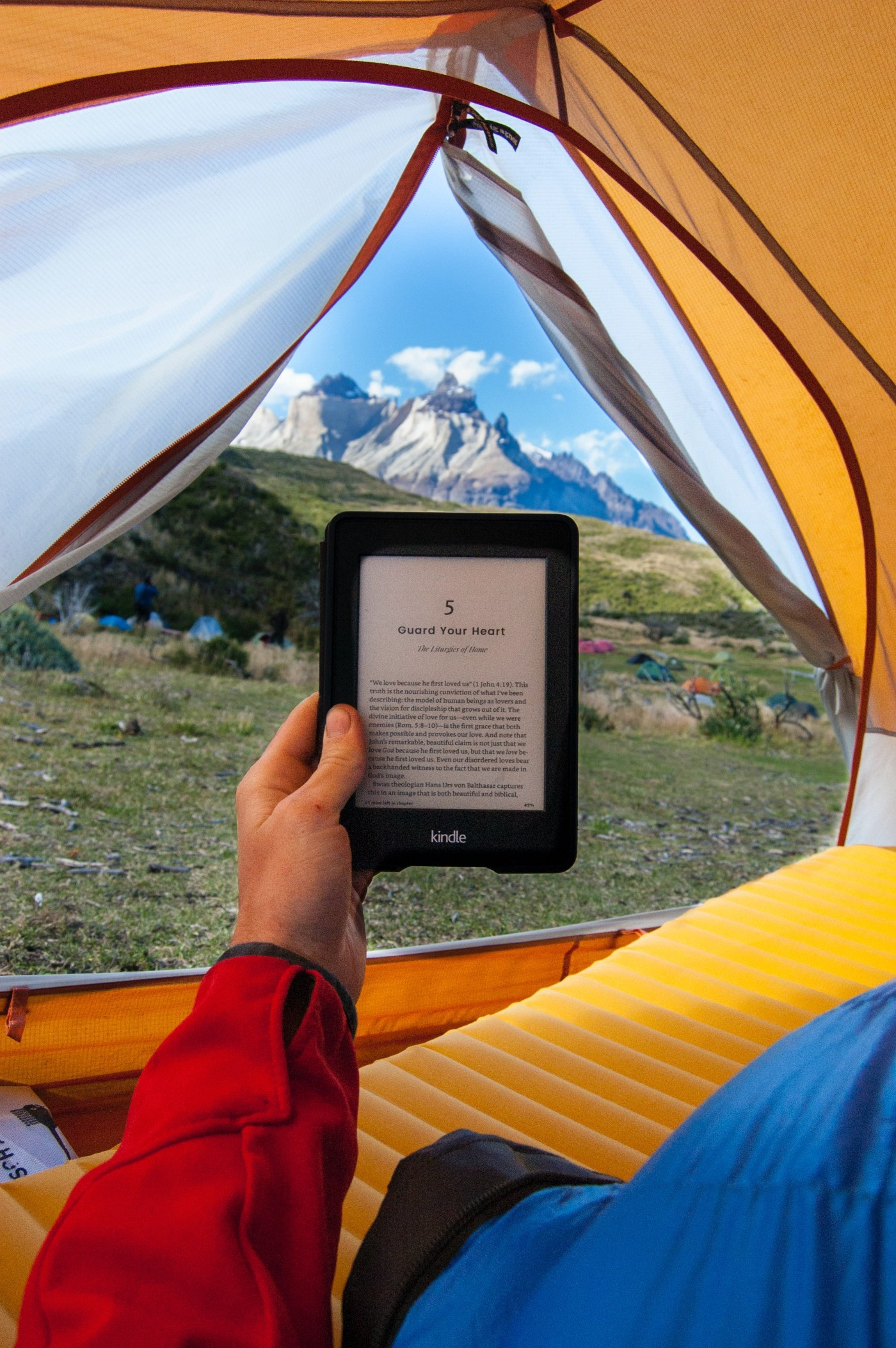 Male hand, holding Kindle device, inside brightly colored tent, looking at tall mountain in the background