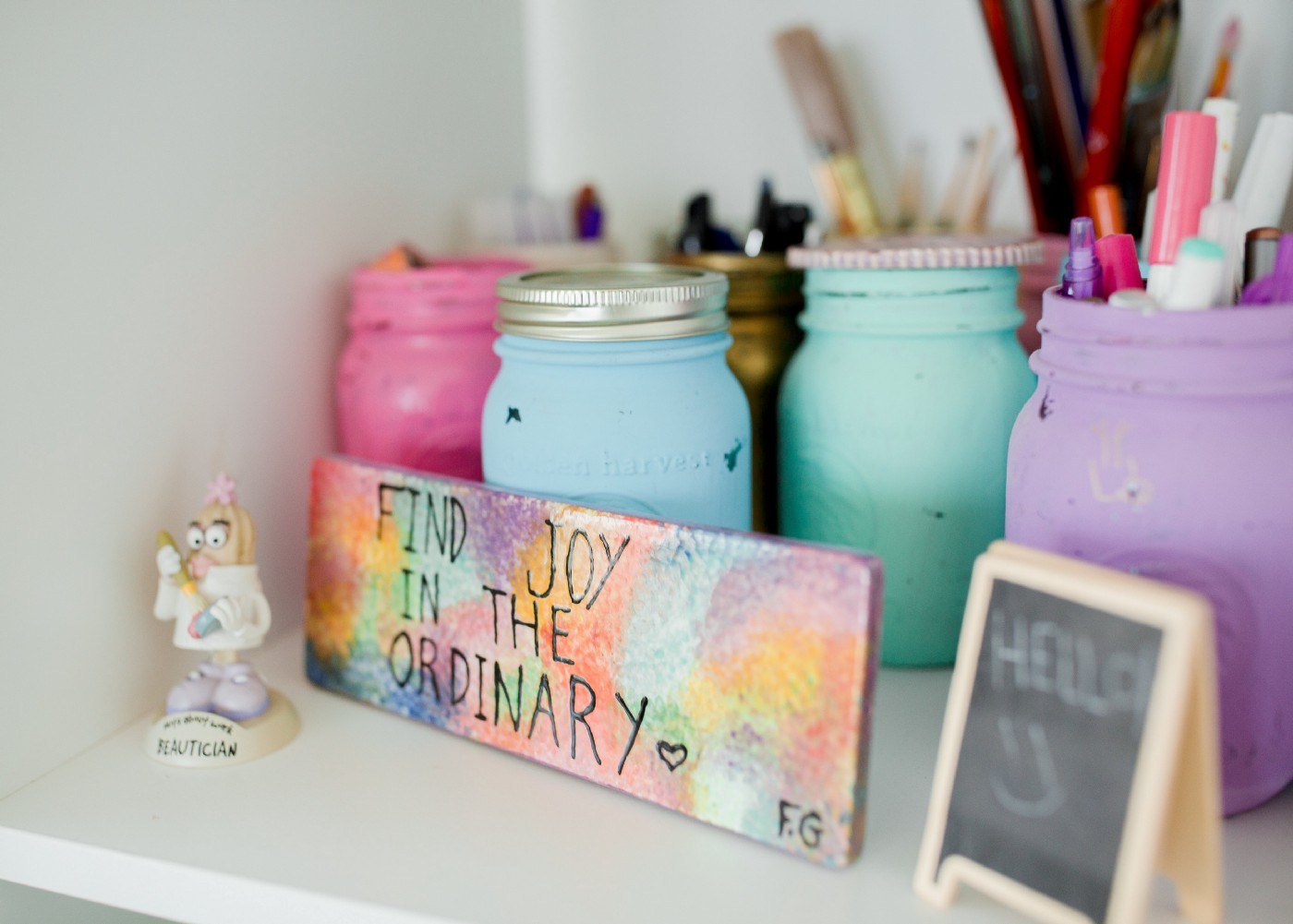 A white shelf with painted mason jars with a colorful sign in front of them that says 'find the joy in the ordinary' and a small figurine beside it.