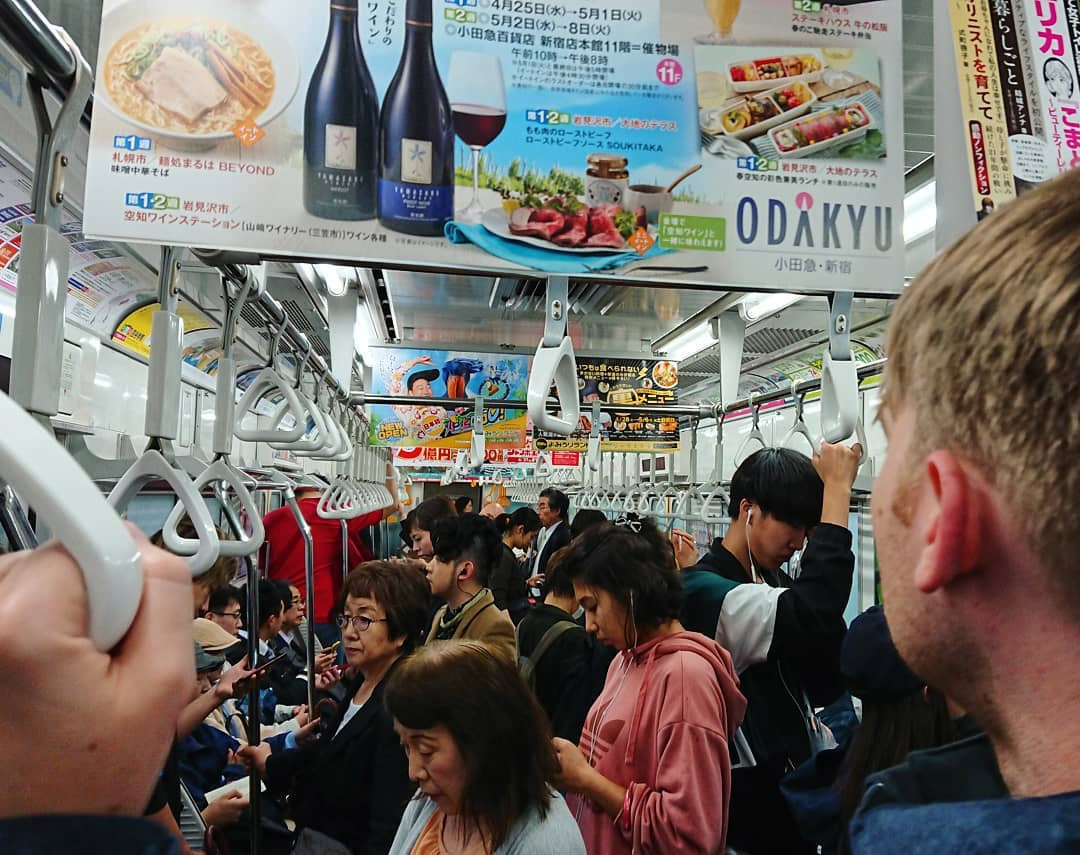 The back of my husband's head as he looks into a packed Tokyo subway train