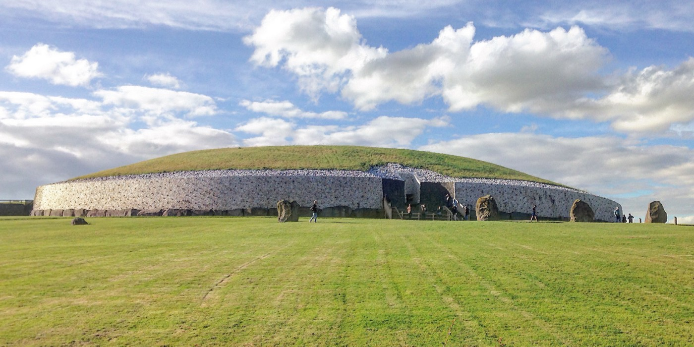 Newgrange Neolithic Passage Tomb—a huge shallow-domed edifice, edges faced in white stone and grass-topped.