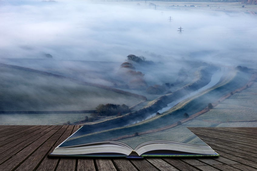 Foggy English countryside landscape at sunrise in winter with layers rollling through the fields coming out of the pages of a magical book lying open on a wooden table.
