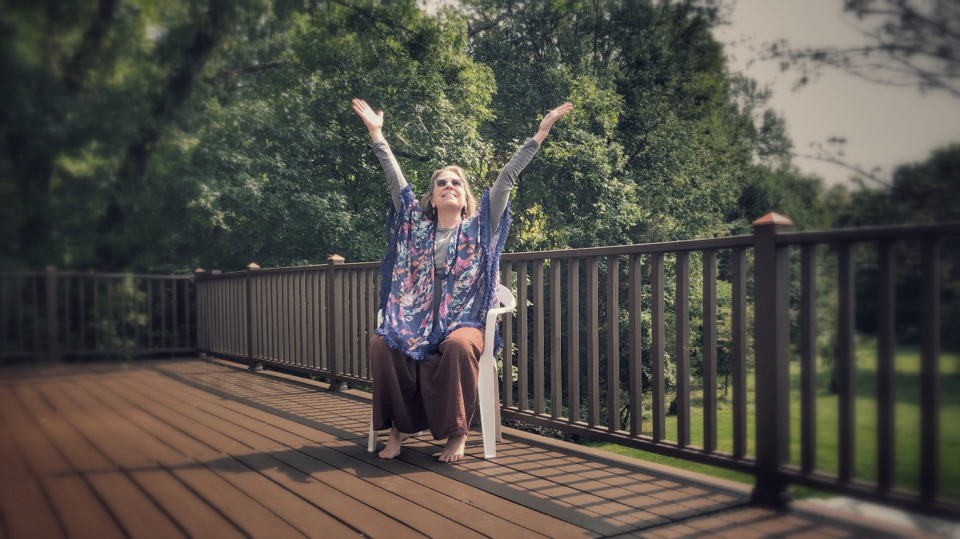 woman sitting on deck raising her hands to the sky in a gesture of happiness