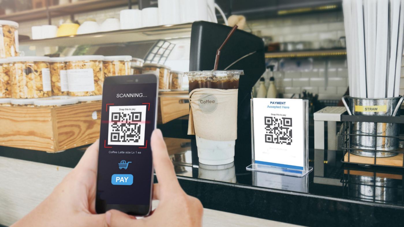 QR payment in a coffee shop through cell phone.—Contactless in F&B industry