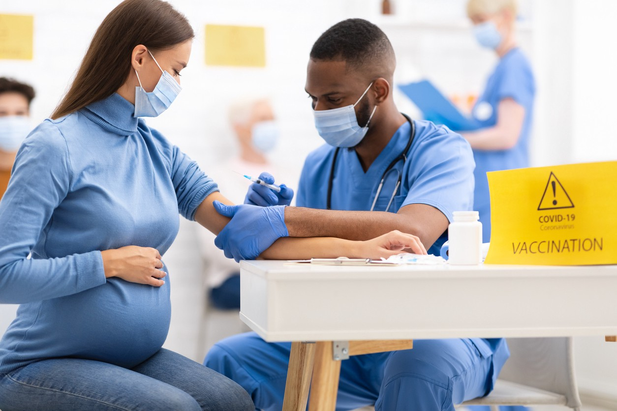 Pregnant Woman Receiving a Coronavirus Vaccine from a health provider