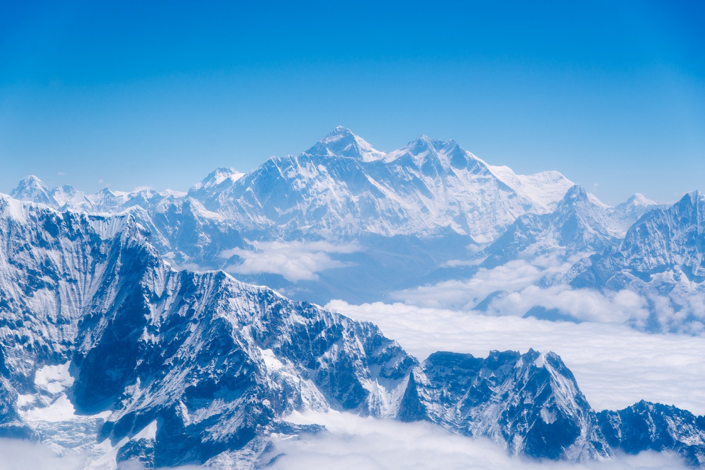 Mount Everest, the tallest mountain in the world, sits in the background covered in snow. Explorers long wanted to climb in the pursuit of human achievement.